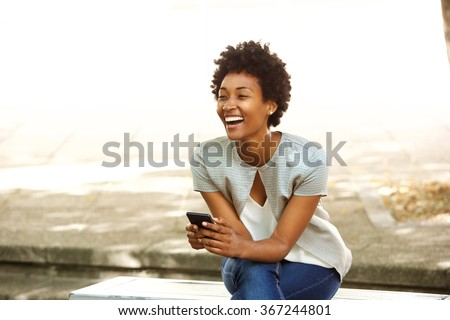 Portrait of beautiful young african woman smiling while sitting outside on a bench holding mobile phone