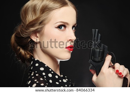 Portrait of beautiful young angry blond woman with revolver in hand - stock photo