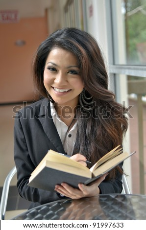 Portrait of beautiful young Asian business woman reading a book with lovely smile