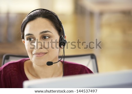 Portrait of beautiful young Asian businesswoman wearing headset in call center