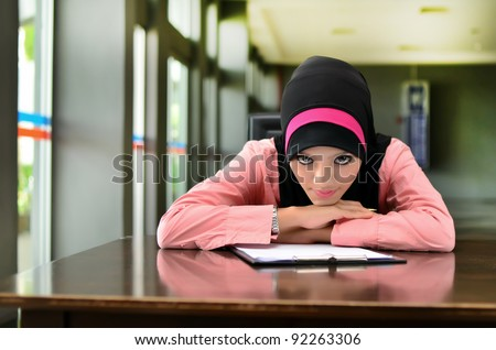 Portrait of beautiful young Asian Muslim student unhappy