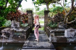 Portrait of beautiful young Asian muslim woman wearing hijab and casual dress standing and pose in garden with pond and water fountain in Bali. Smiling and happy expression. For tourism concept.