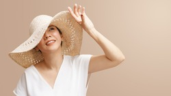 Portrait of beautiful young asian woman wearing straw hat wide brim to protect her flawless face from ultraviolet in the sunlight. Facial Sunscreens, SPF, Sunspots, Treatments, Skin care products.