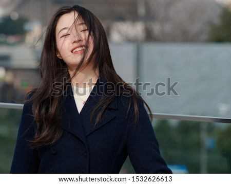 Portrait of beautiful young Asian woman with black long hair, smiling and happy in wind with blur background.