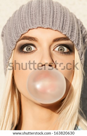 Portrait of beautiful young blond girl in beanie hat blows big bubble from bubble gum
