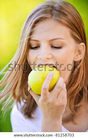 portrait of beautiful young blond woman eating fresh green apple at park
