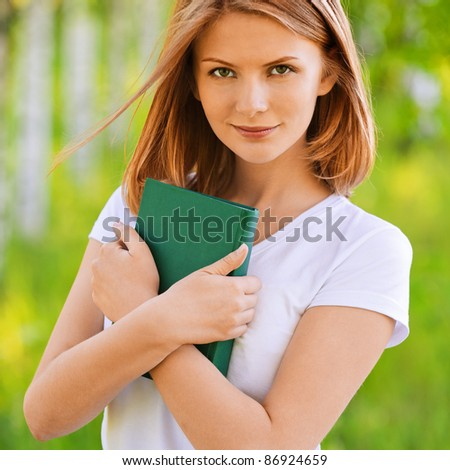 portrait of beautiful young blond woman holding book in summer green park