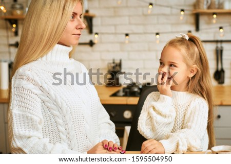 Portrait of beautiful young blonde female having funny face, making her adorable baby daughter laugh. Playful little girl sitting in kitchen, covering mouth and looking at mother. People and family