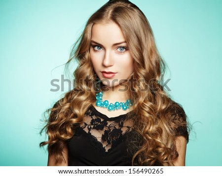 Stock Photo Portrait of beautiful young blonde girl in black dress. Fashion photo