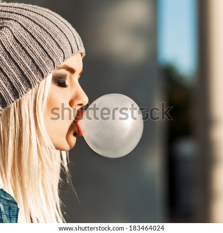 Portrait of beautiful young blonde teenage girl in beanie hat blows big bubble from bubble gum