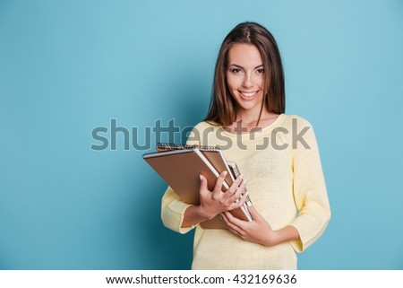 Portrait of beautiful young brunette holding notebooks isolated on the blue background