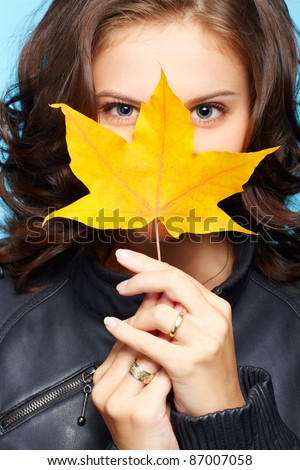 portrait of beautiful young brunette woman in black leather jacket hiding face behind yellow autumn maple leaf