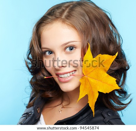portrait of beautiful young brunette woman in black leather jacket with yellow autumn maple leaf in teeth