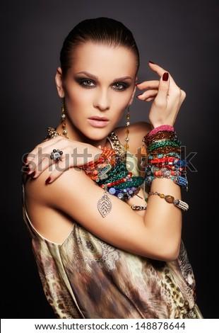 portrait of beautiful young brunette woman in ear-rings and multiple bracelets on dark gray