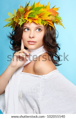 portrait of beautiful young brunette woman in garland of autumn maple and fern leaves