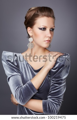 portrait of beautiful young brunette woman in stylish dress touching shoulder