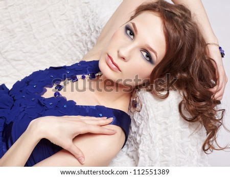 portrait of beautiful young brunette woman relaxing in blue dress and beads