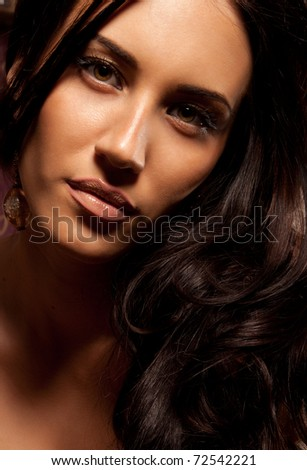 Portrait of beautiful young brunette woman with curly hair