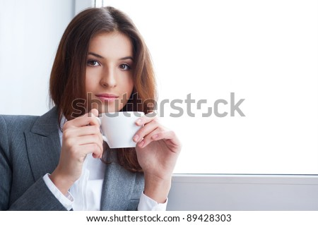Portrait of beautiful young business woman wearing formal clothes drinking coffee while resting at her office near big window