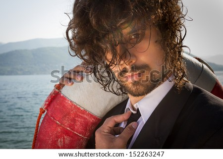 Portrait of beautiful young Businessman with long hair, standing next to the sea, holding red and white life belt with proud smile on his face, victorious. Tough Business. Business Insurance.