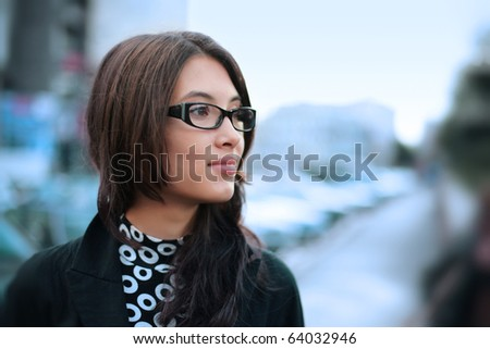 Portrait of beautiful young businesswoman outdoor over blurred street background. Closeup, shallow DOF. - stock photo