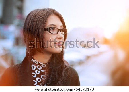 Portrait of beautiful young businesswoman outdoor over blurred street background. Closeup, shallow DOF.