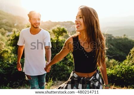 Portrait of beautiful young couple enjoying nature at mountain peak.