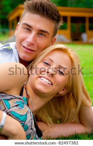 Portrait of beautiful young couple sitting on ground in park relaxing