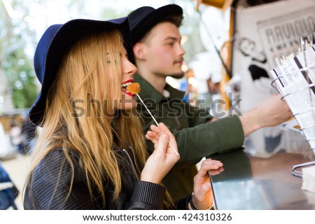 Portrait of beautiful young couple visiting eat market in the street. #424310326