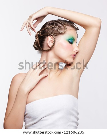 portrait of beautiful young dark blonde woman with creative braid hairdo and green eye shades touching her neck