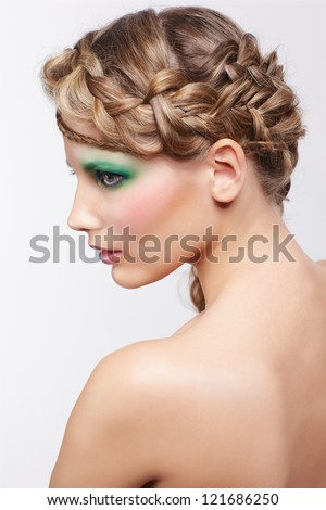 Stock Photo portrait of beautiful young dark blonde woman with creative plait hairdo and green eye shades make up on gray