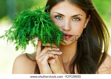 portrait of beautiful young dark-haired sexy girl seductively baring her shoulders with bundle of herbs (dill) in hands