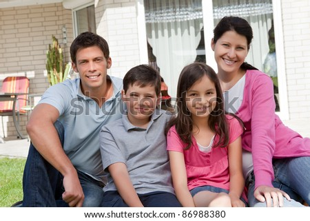 Portrait of beautiful young family of four sitting together outside their home - stock photo
