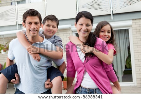 Portrait of beautiful young family together outside their house