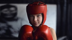 Portrait of beautiful young female boxer. Young boxer woman with red boxing gloves, headgear standing in guard position.