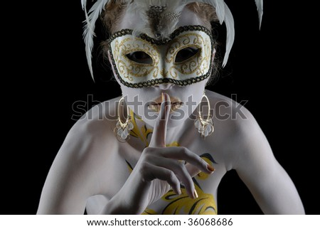 Portrait of beautiful young girl in gold flowers bodyart in venice mask holding finger at her lips