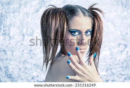 Portrait of beautiful young girl model with pigtails, bright fancy makeup and blue manicure over a blurred metallic background