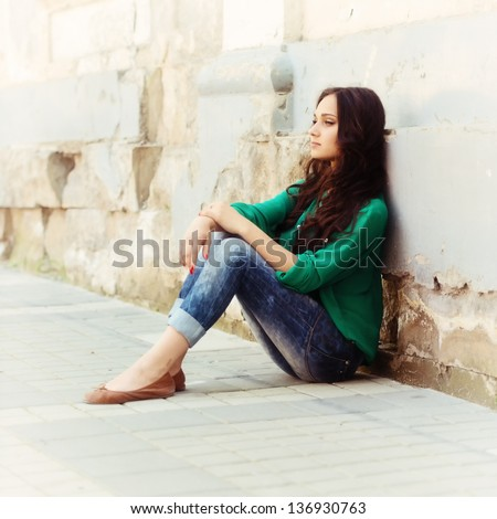 Portrait of beautiful young girl, sitting leaning on an old wall