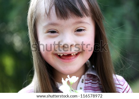 Portrait of beautiful young girl smiling with flowers in the park