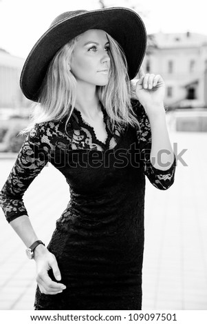 Portrait of beautiful young girl standing in black sun hat outdoors