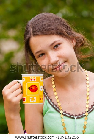 Portrait of beautiful young girl with a yellow cup outdoors