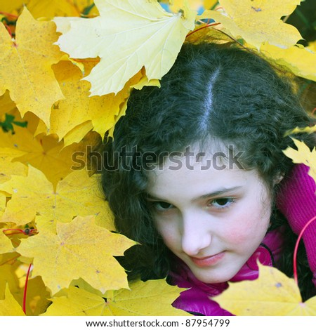 Portrait of beautiful young girl with the yellow leaves in autumn. - stock photo