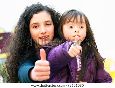 Portrait of beautiful young girls giving thumbs in the playground .