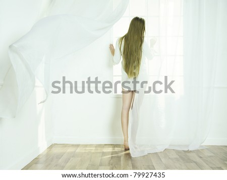 Portrait of beautiful young girls in the interior of the window