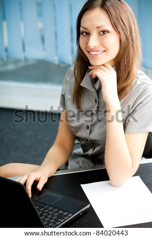 Portrait of beautiful young happy smiling business woman at office
