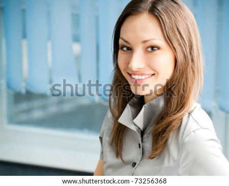Portrait of beautiful young happy smiling business woman at office. You can use left part for slogan, big text or banner.