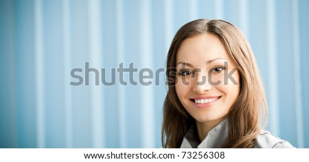 Portrait of beautiful young happy smiling businesswoman at office.To provide maximum quality, I have made this image by combination of two photos. You can use left part for slogan, big text or banner.