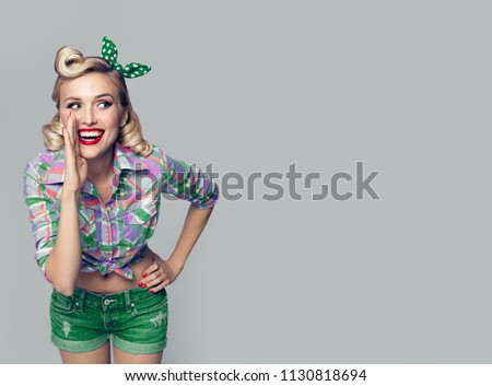 Portrait of beautiful young happy smiling woman, dressed in pin-up style. Caucasian blond model posing in retro fashion and vintage concept studio shoot, on grey background. Copyspace.
