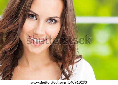 Portrait of beautiful young happy smiling woman, outdoors, with copyspace