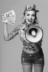 Portrait of beautiful young happy smiling woman with money and megaphone, dressed in pin-up style. Caucasian blond model posing in retro fashion and vintage concept. Black and white.